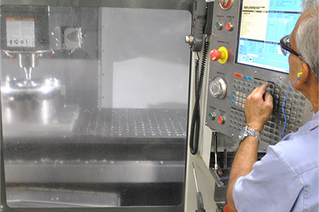 A technician is machining an aluminum cast-in heated chuck during a semi product manufacturing session at CAS in Batavia.